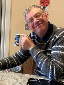 Robert smiling and drinking a cup of tea