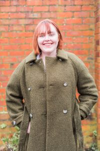 Molly wearing a green coat and a big smile